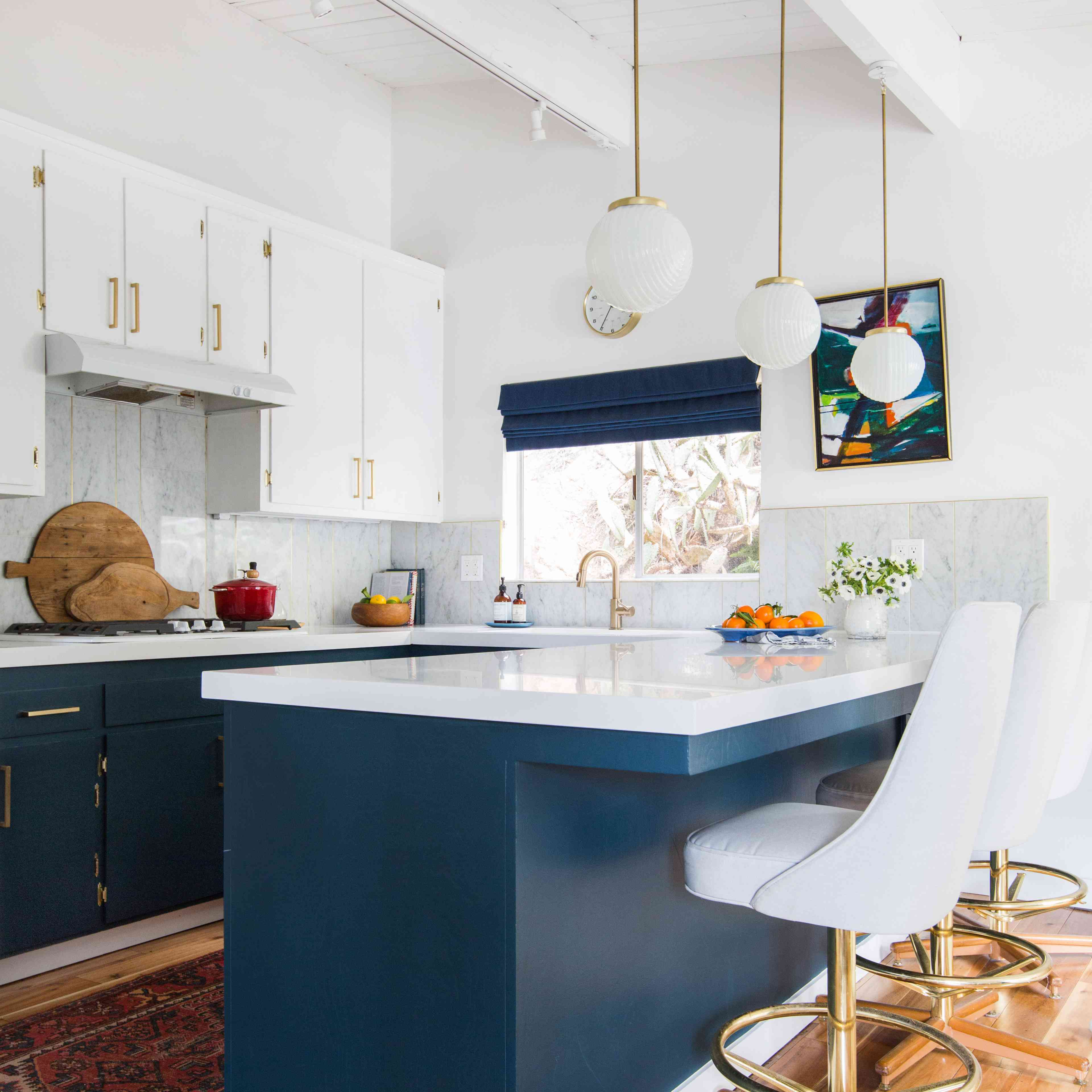 kitchen with blue and white cabinets and blue window treatment