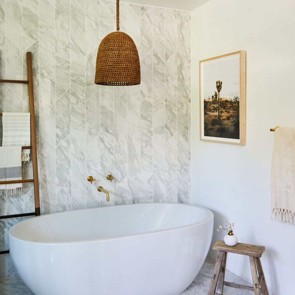 An all-white bathroom with a woven light fixture