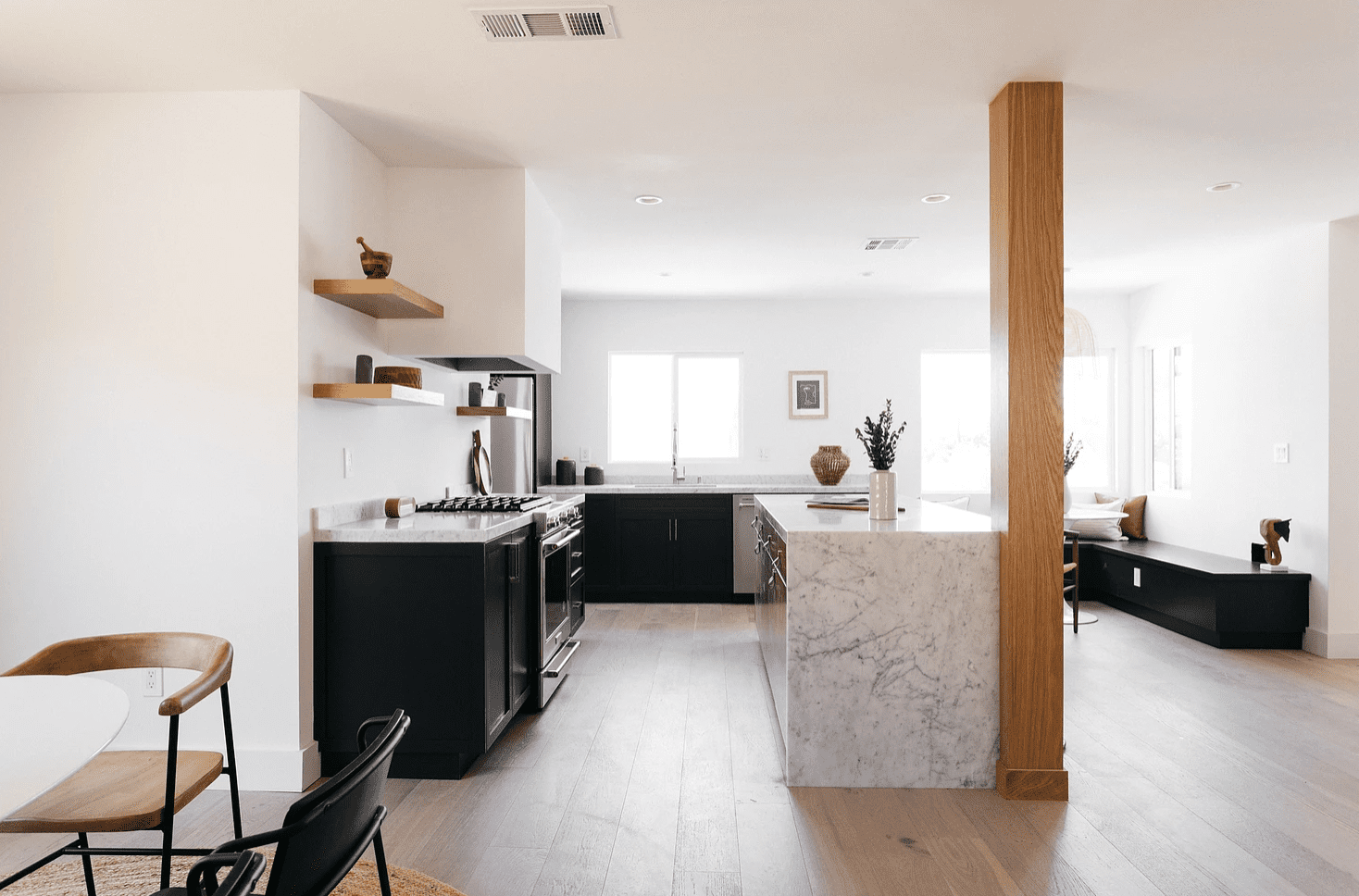 An open-concept kitchen with an exposed wooden column