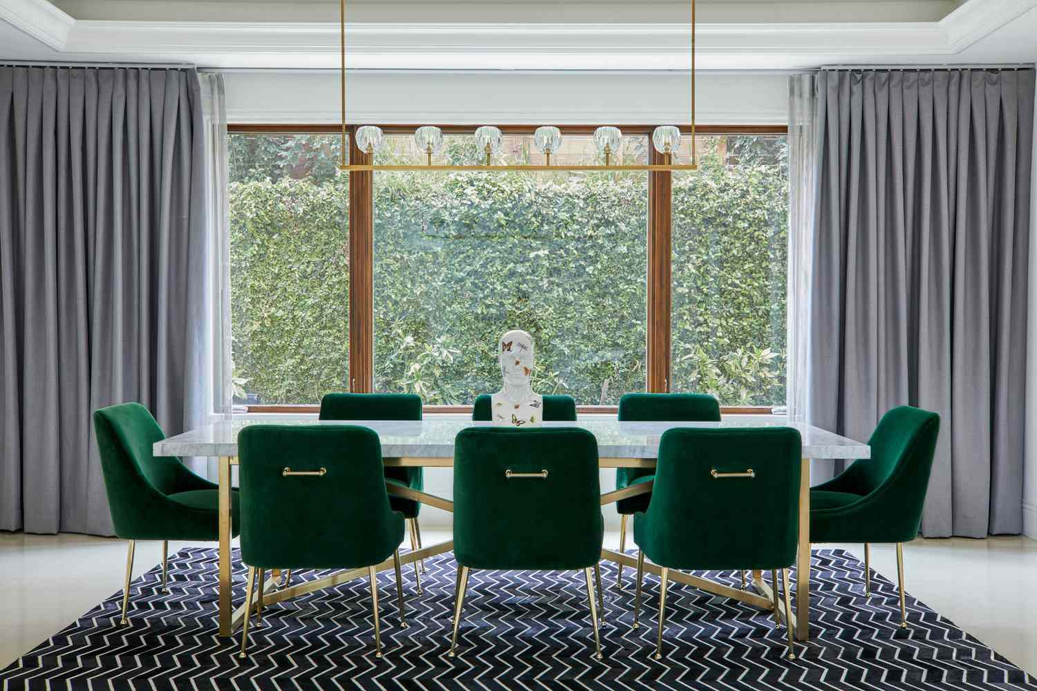 A dining room with a navy rug and blue-gray curtains lining the walls