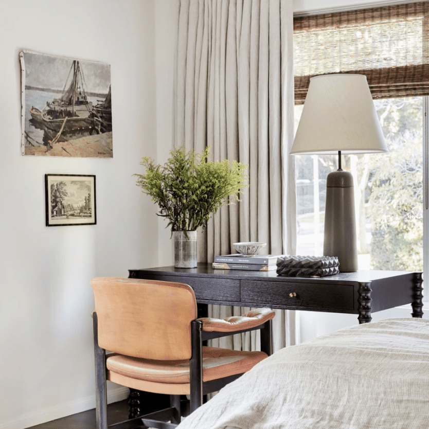 A bedroom with a desk tucked into the corner