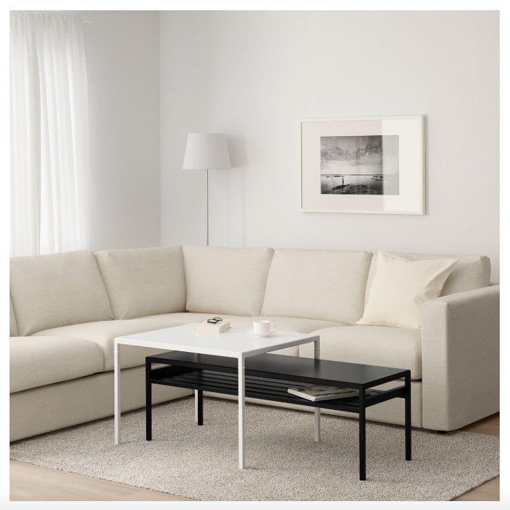 One square white nesting table over one rectangular black table.