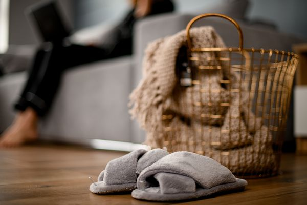 Large metal wicker basket with knitted blanket inside and slippers nearby
