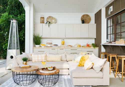 Sunny and bright outdoor patio with beige couch.