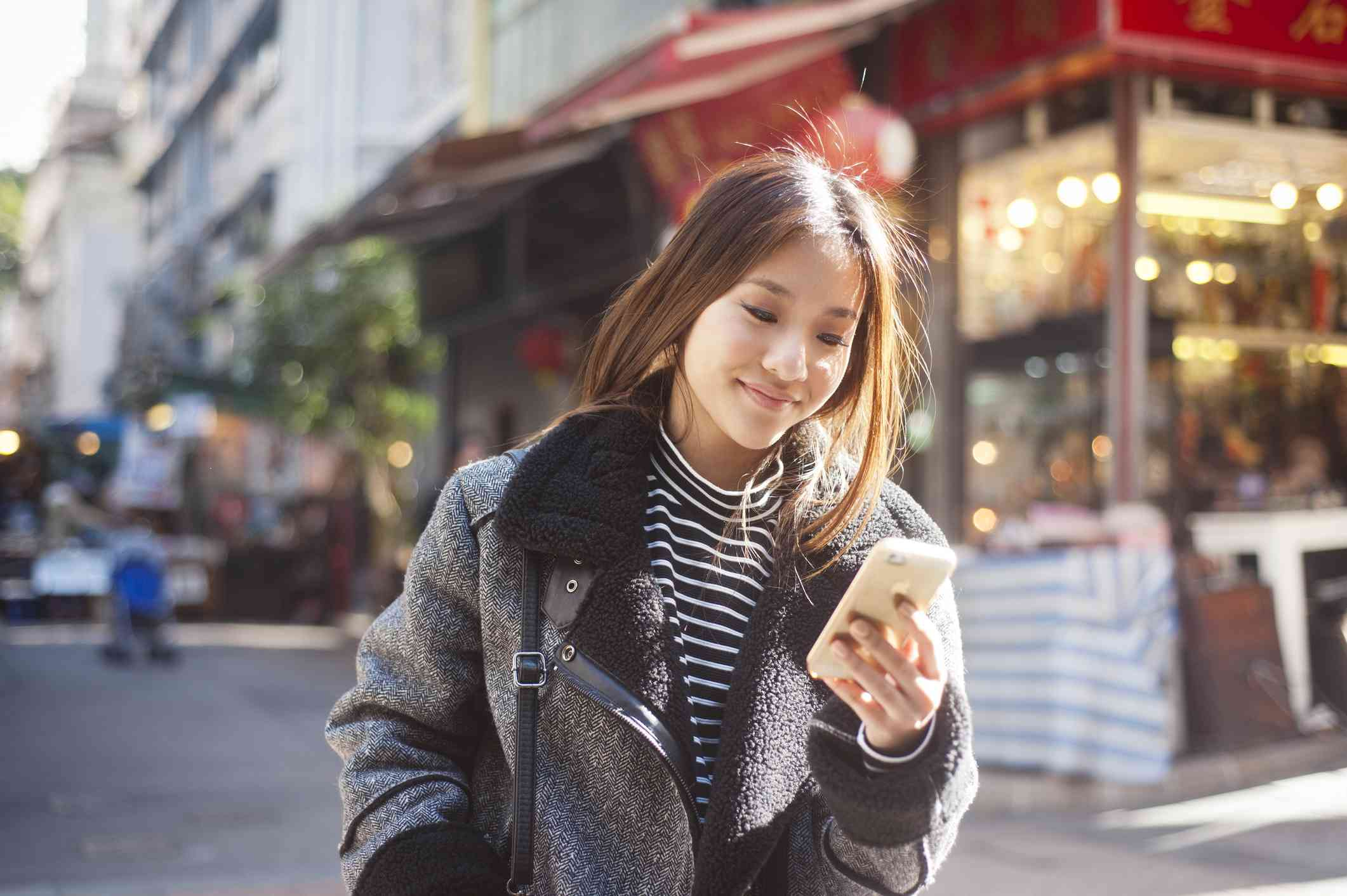 young person in fur jacket on the street looking at iPhone