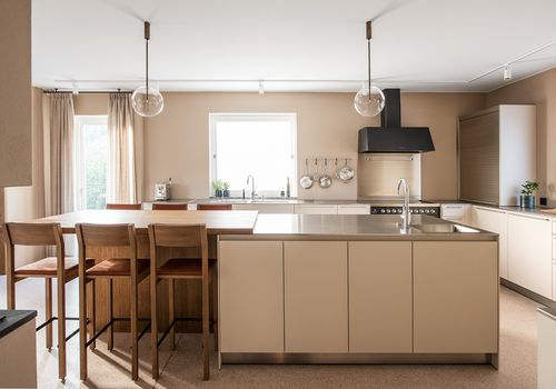 Modern taupe and cream kitchen with minimal glass orb pendants and track lighting
