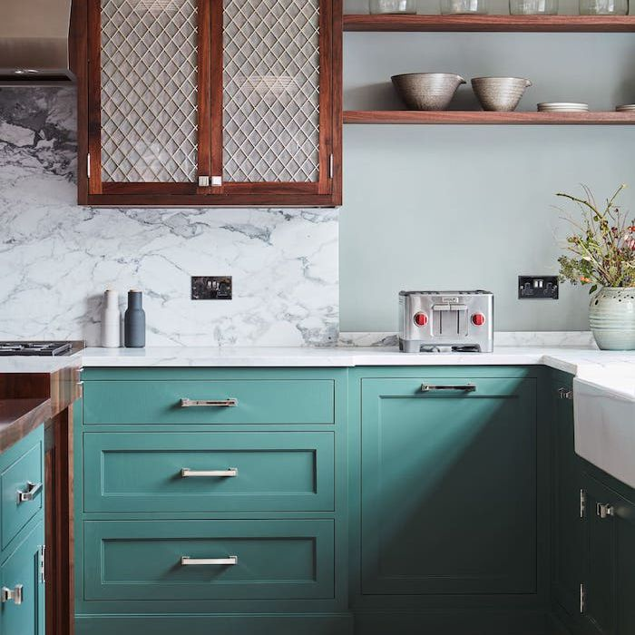Teal lower cabinets paired with dark wooden upper cabinets, white marble backsplash and light gray walls