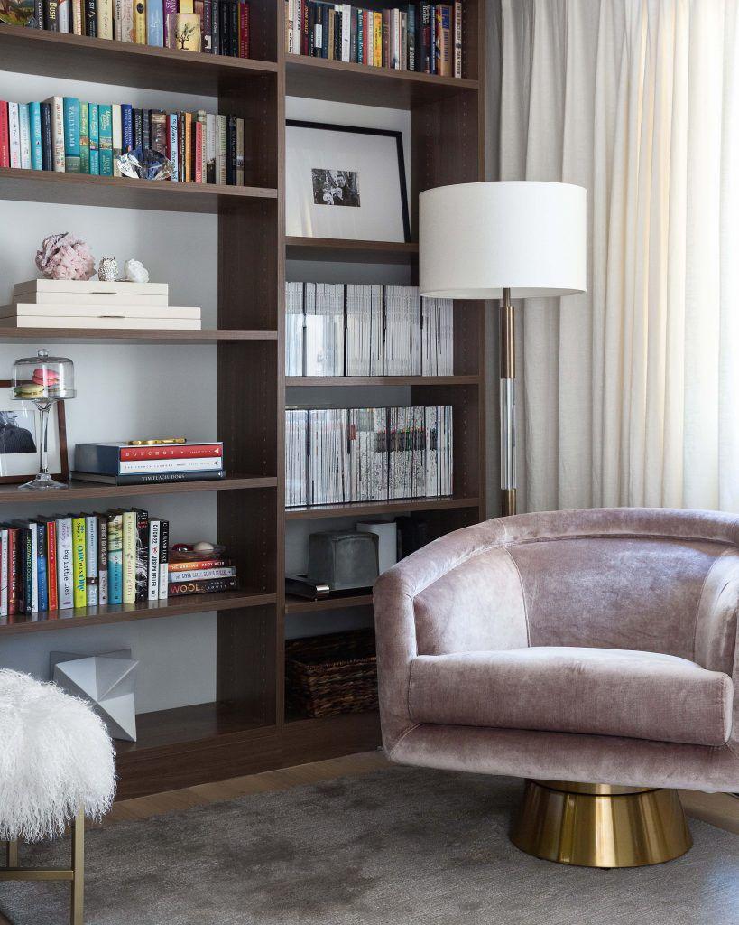 Tall wooden bookcase behind a velvet armchair
