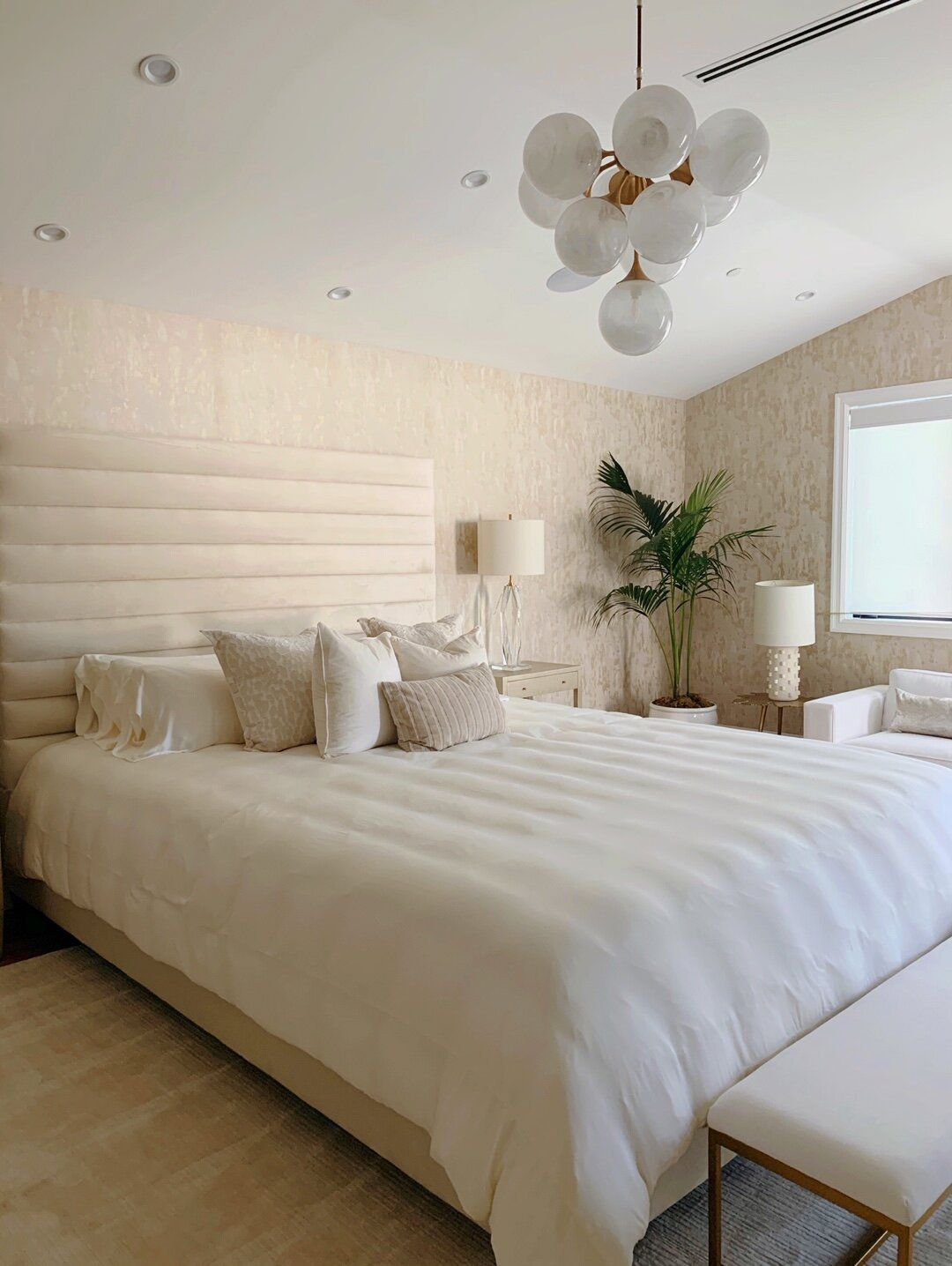 A neutral bedroom with a modern globe pendant light.