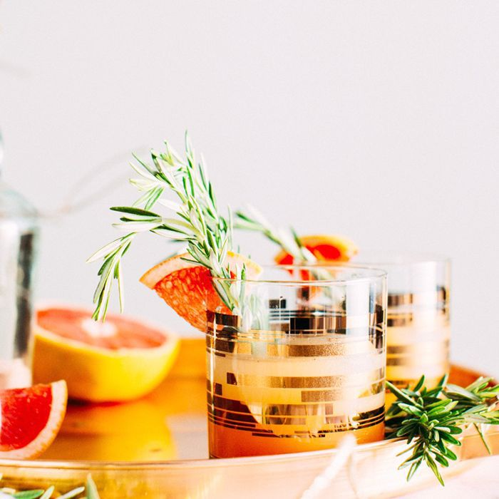 A round copper bar tray with a whiskey sour and a grapefruit slice with rosemary garnish in a pretty lowball glass.