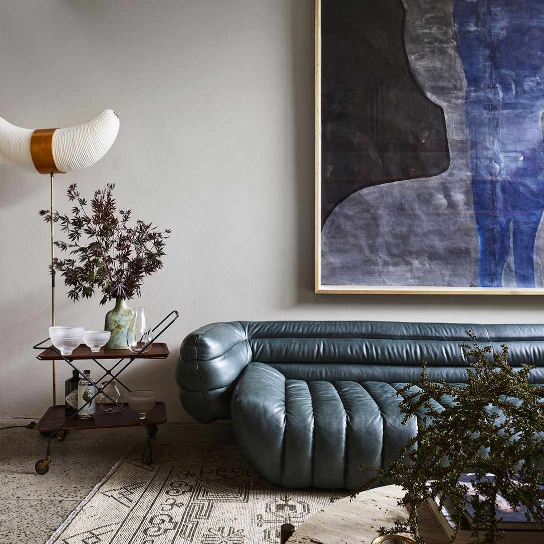 A midcentury living room with a warm, denim blue, channel-tufted leather couch and a large blue abstract painting on the wall.