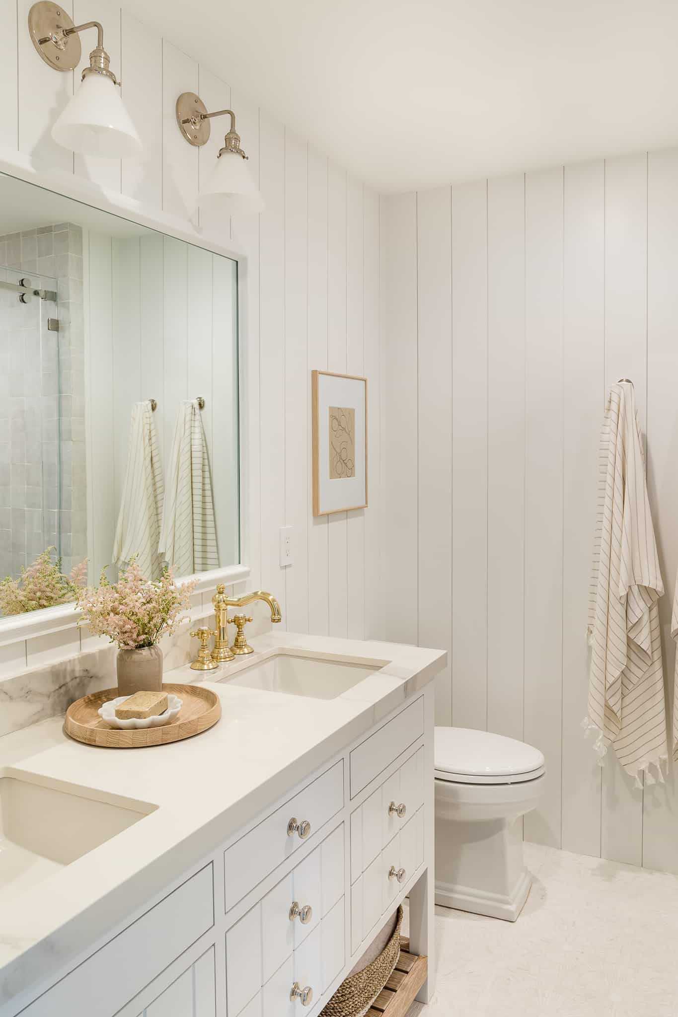 A small primary bathroom lined with a crisp all-white palette