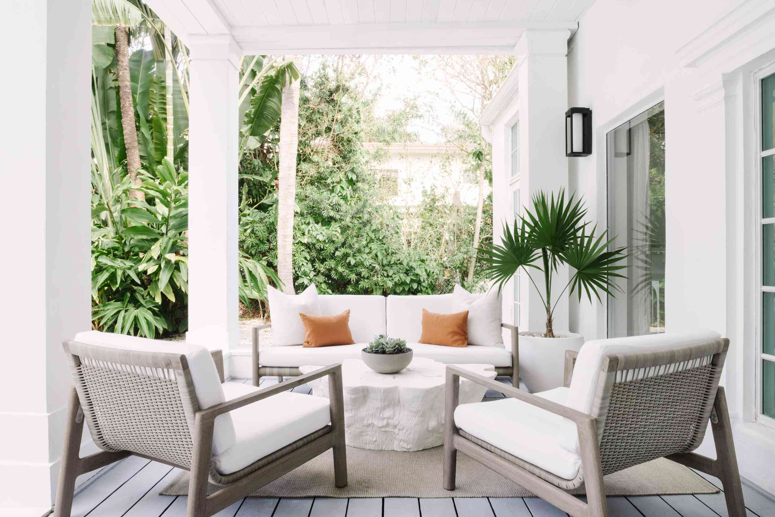 Outdoor lounge space with white sofa and chairs.