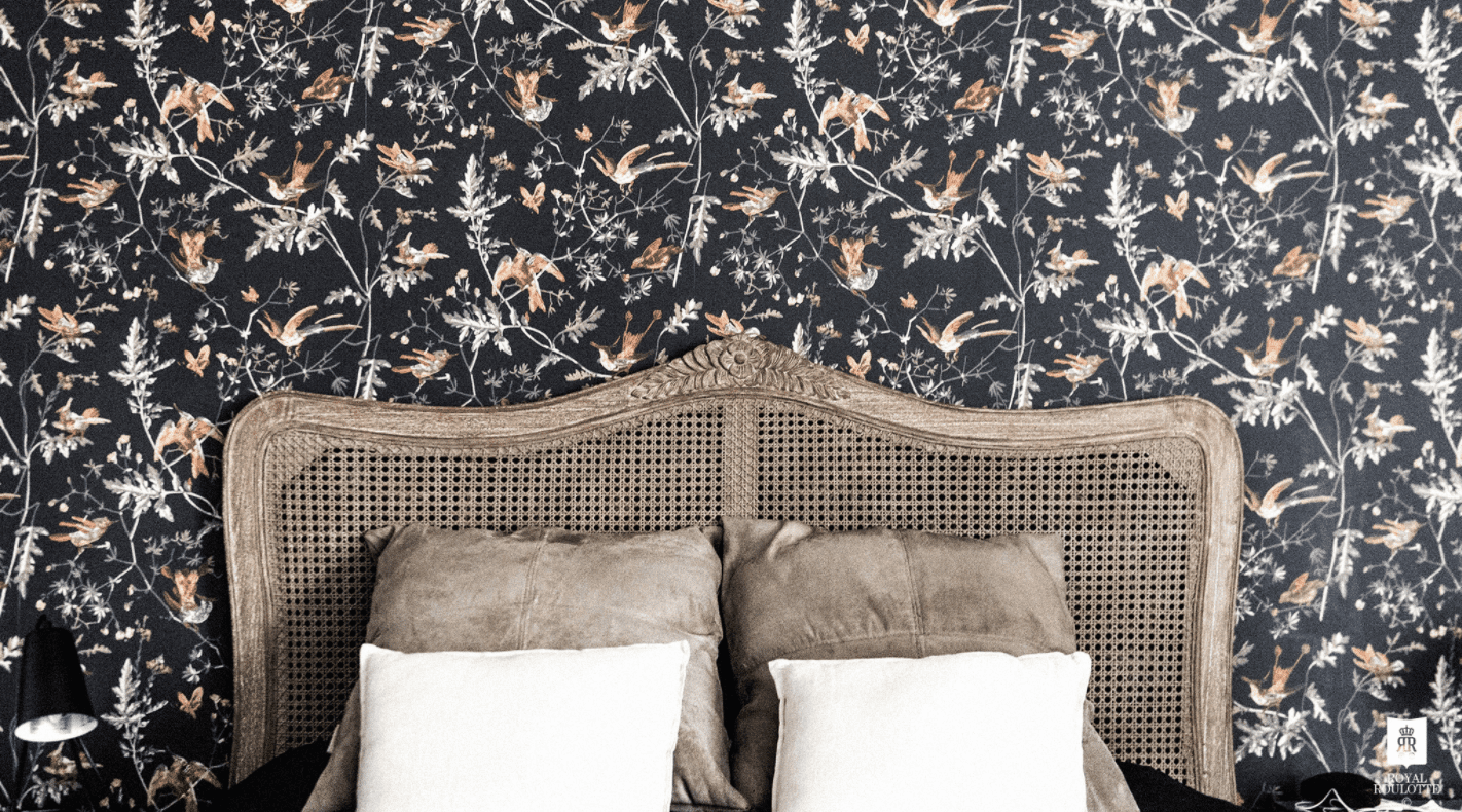 A bedroom with a bohemian, but Victorian-inspired headboard and floral wallpaper