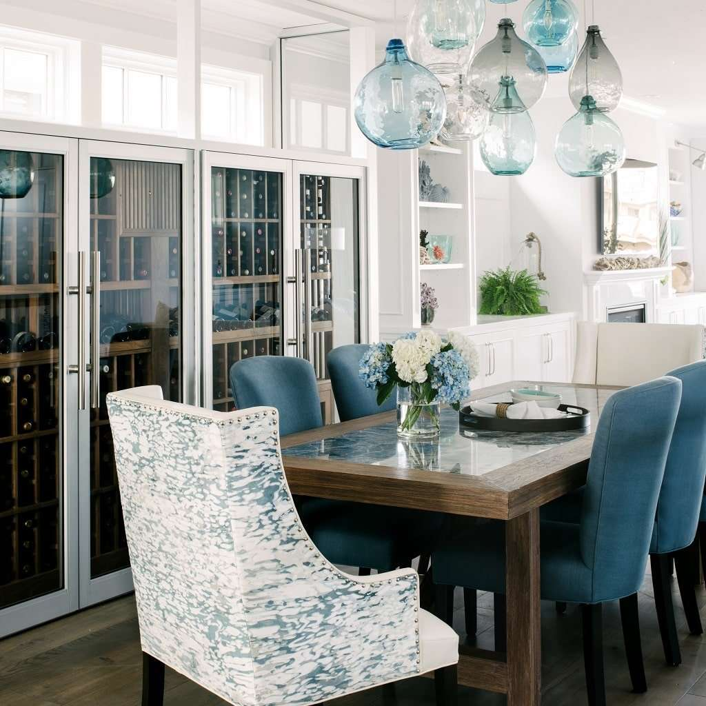 A dining room decorated with a vibrant blue chandelier and several blue upholstered chairs
