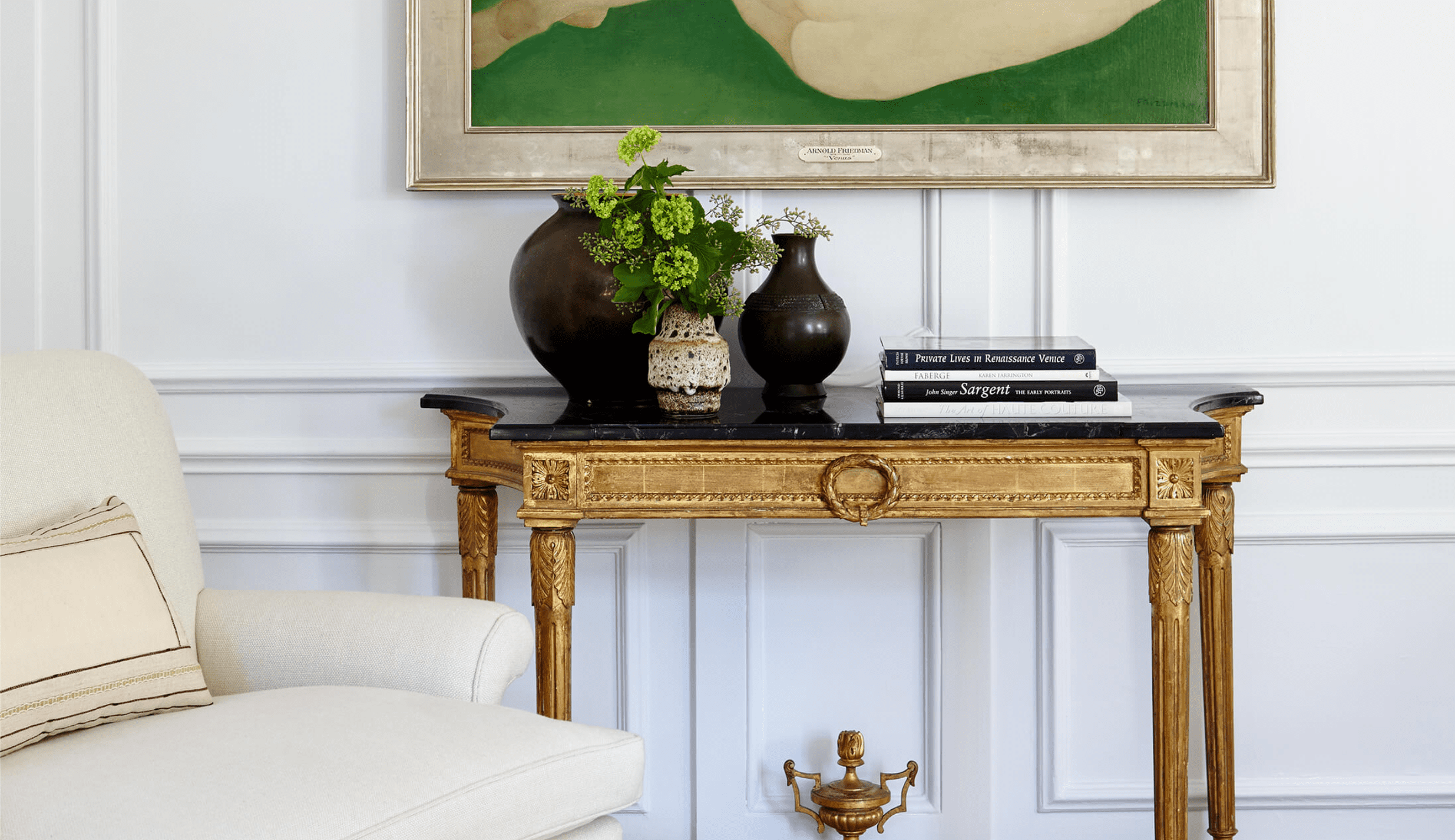 A gold console table in a room lined with crown molding