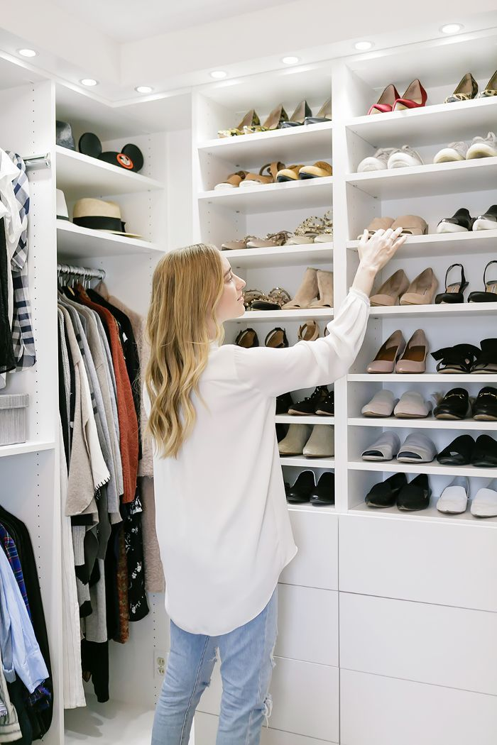 Fashion blogger in front of her walk-in closet shoe shelves
