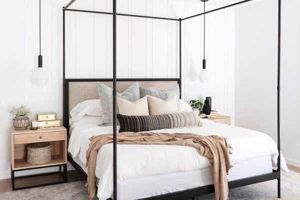 white bedroom with black canopy bed