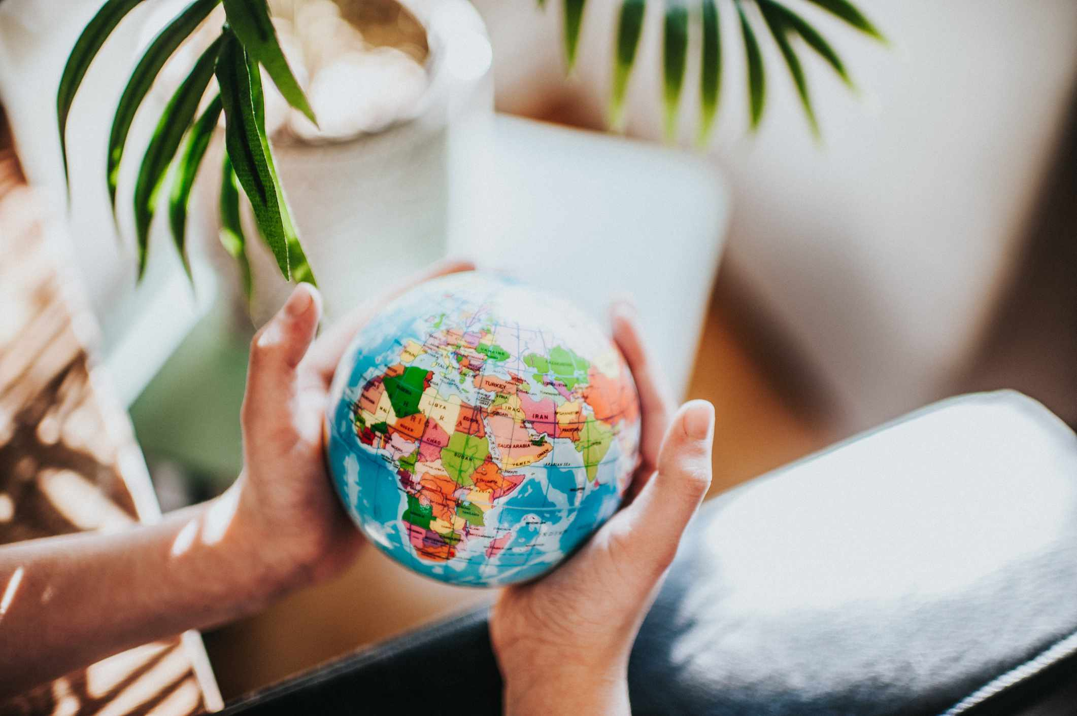 Hands hold small globe