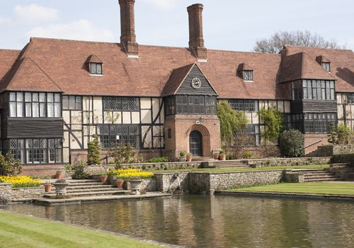 A Mock Tudor-style house in front of a pond