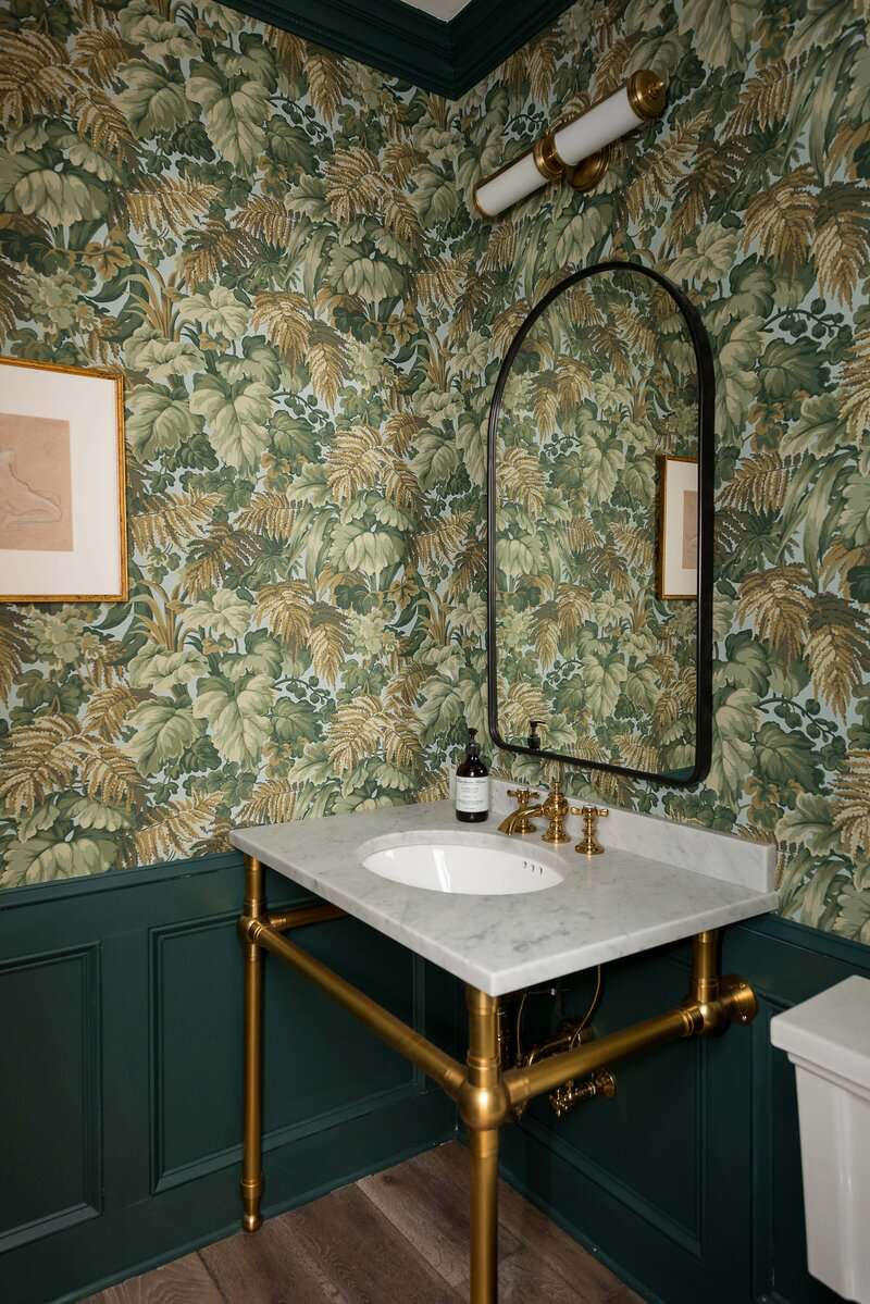 A powder room lined with bold printed wallpaper
