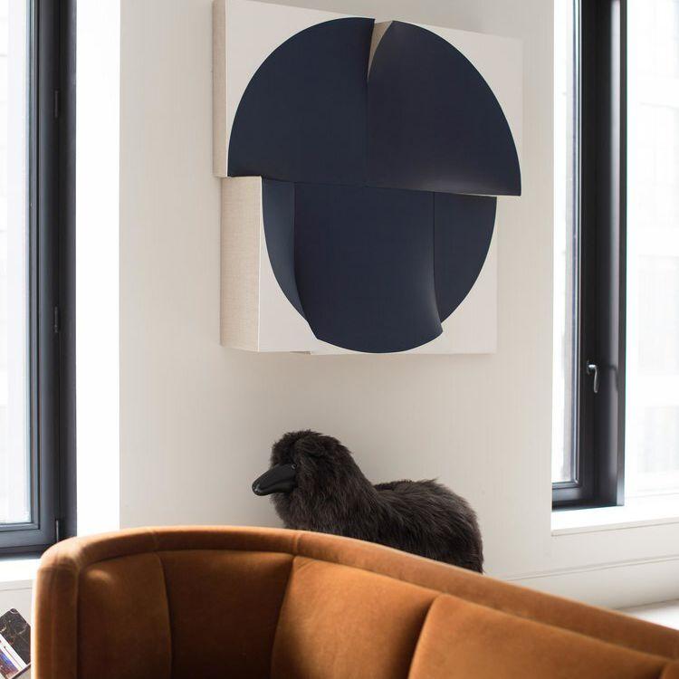 A room with a dark orange sofa and a work of modern art