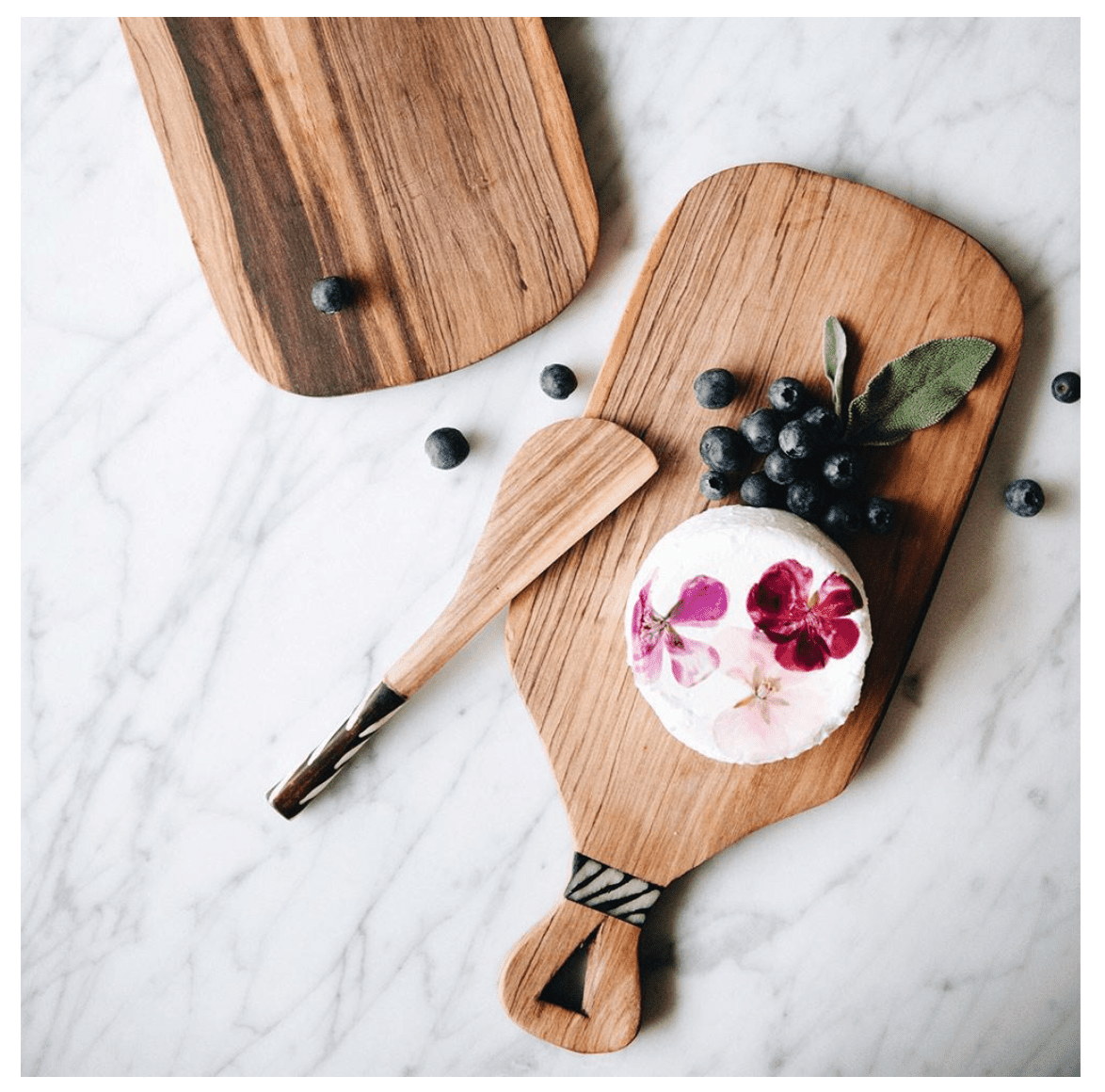 Cheese board plated with blueberries and rind of white cheese with floral imprint