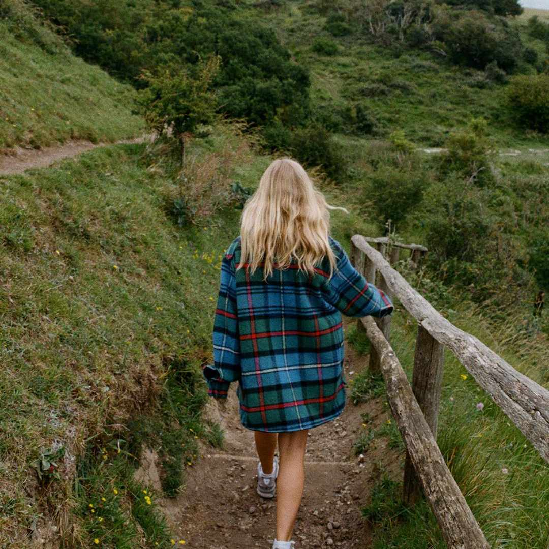 Woman hiking in flannel shirt.