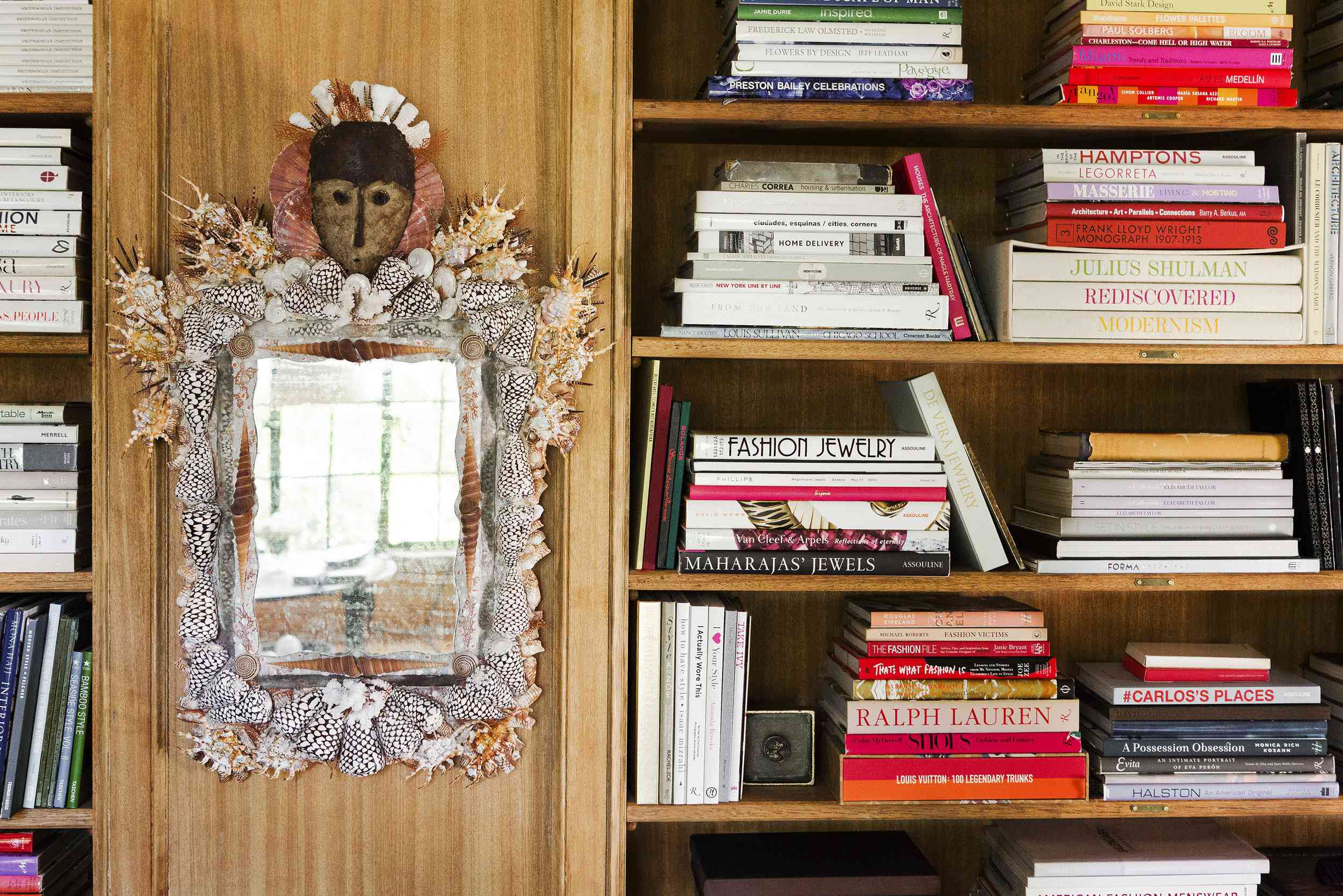 Wooden built-in bookshelves in an eclectic space with a quirky folk-art mirror bedecked in seashells.