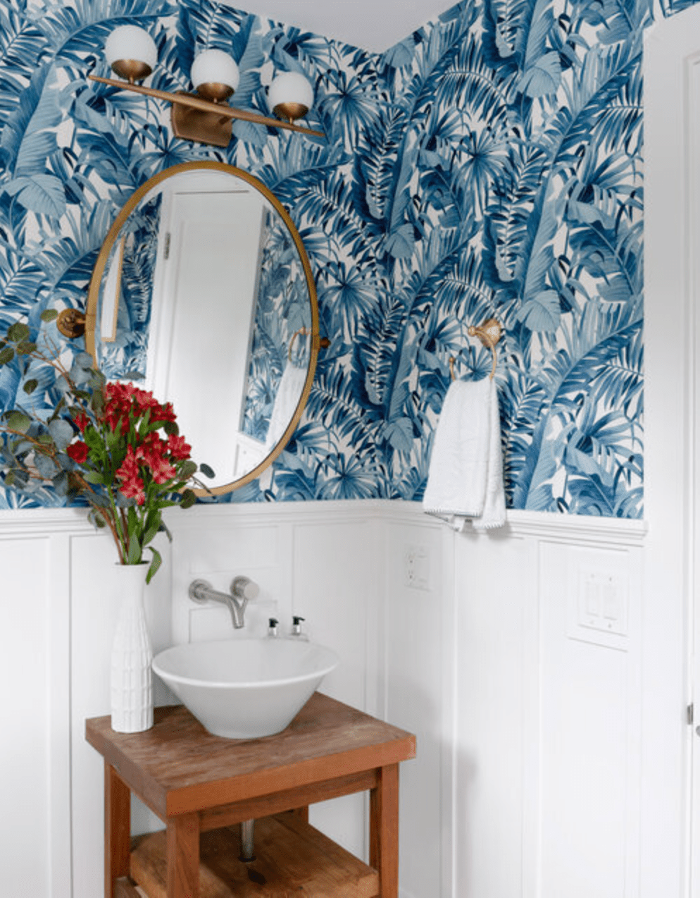 Moderin bathroom with mixed metal fixtures, blue palm leaf patterned wallpaper