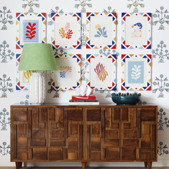 A maximalist room with printed wallpaper and several bold prints