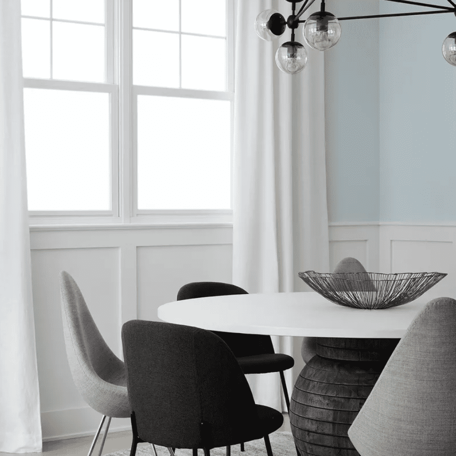A dining room with white, gray, and black furniture and light blue walls