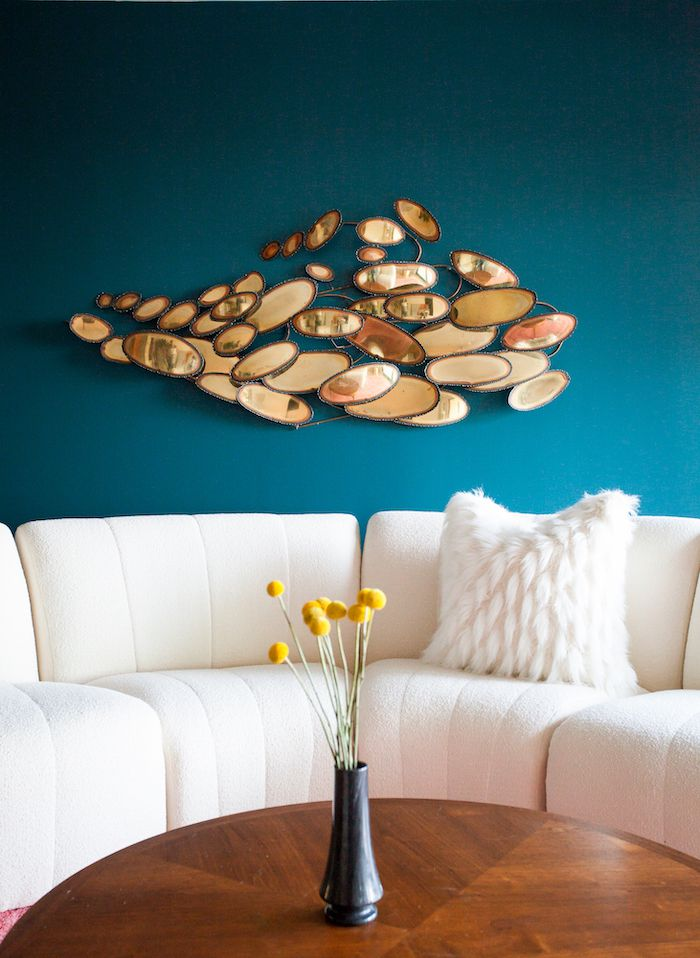 midcentury modern living room, white cushion sofa, abstract art sculpture on the wall