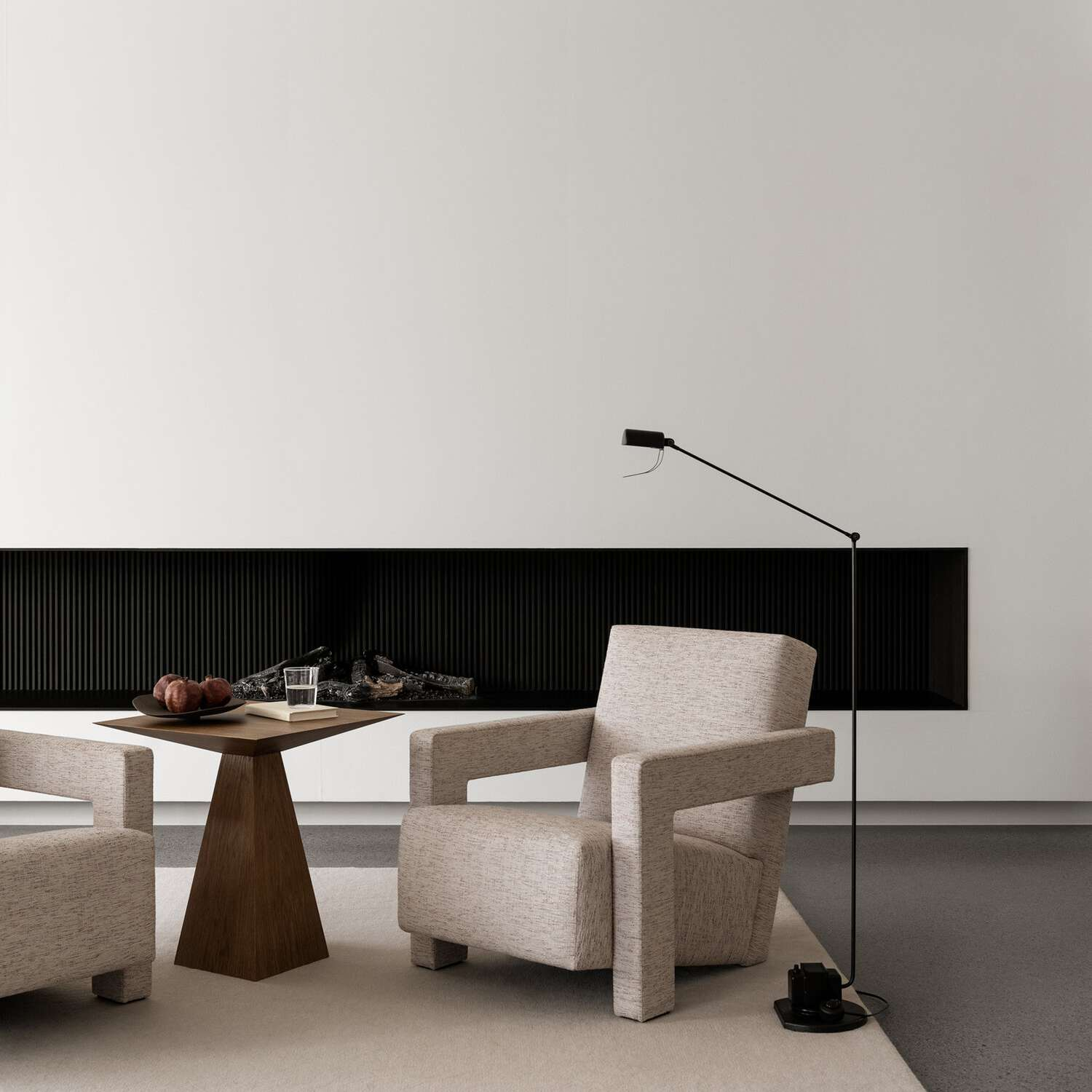 A living room with sleek furniture and cement floors adorned with a rug