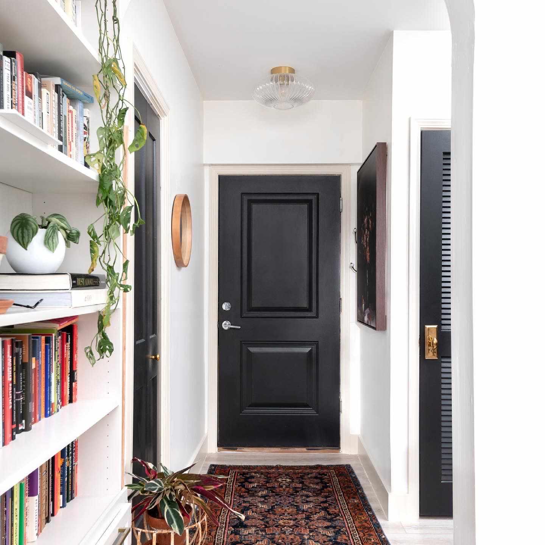 Black door in white entryway with bookshelf.