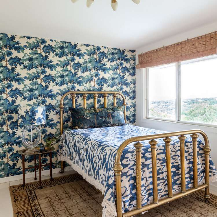 Bright, floral blue bedroom with overhead chandelier and big window.
