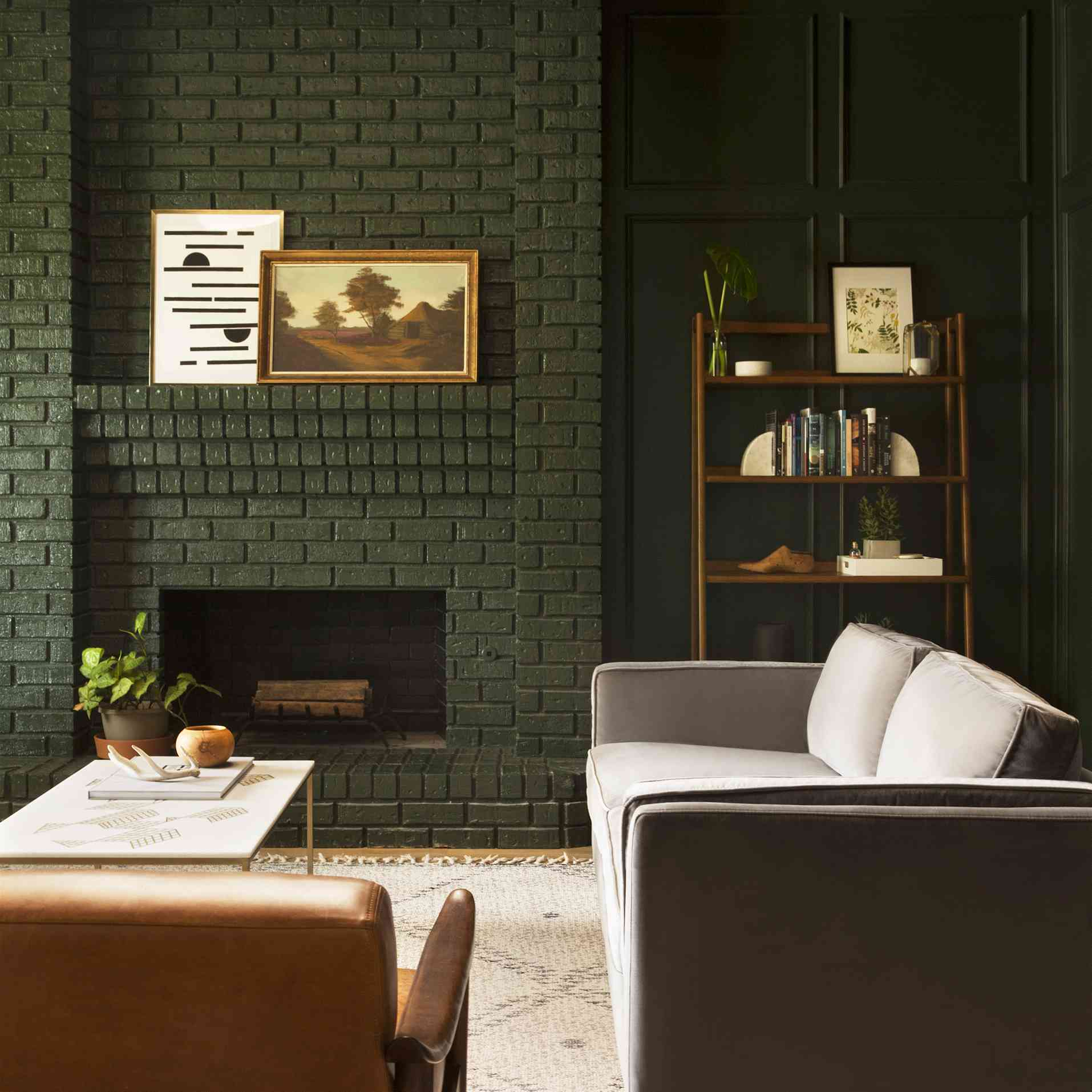 Dark green living room with painted brick fireplace and panelling