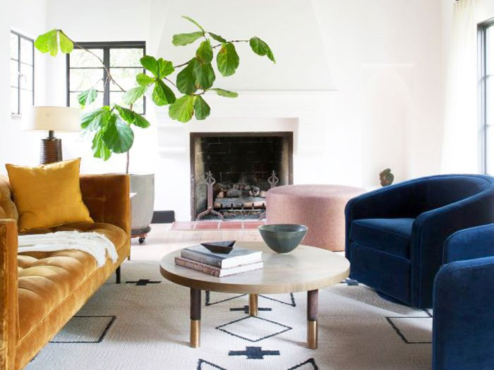 a living room with a graphic rug and colorful furniture