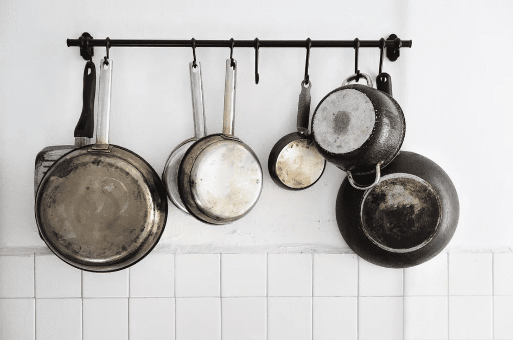 how to clean a burnt pot - burnt pots and pans hanging in kitchen