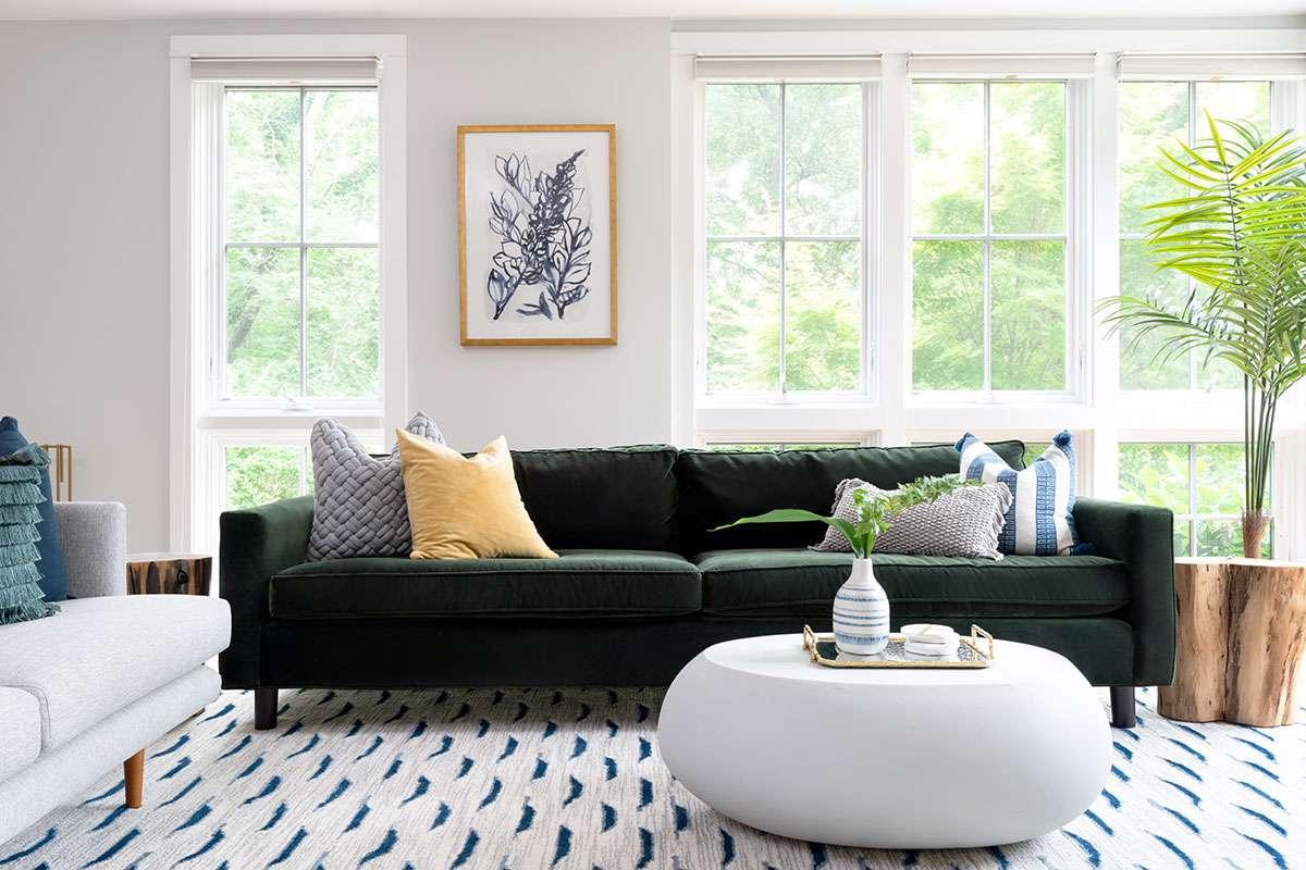 Cozy asymmetrical living room with green velvet sofa