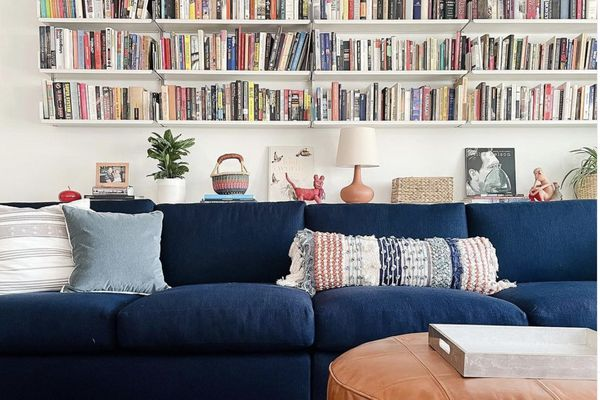 living room with dark blue couch, floating bookshelves on wall behind