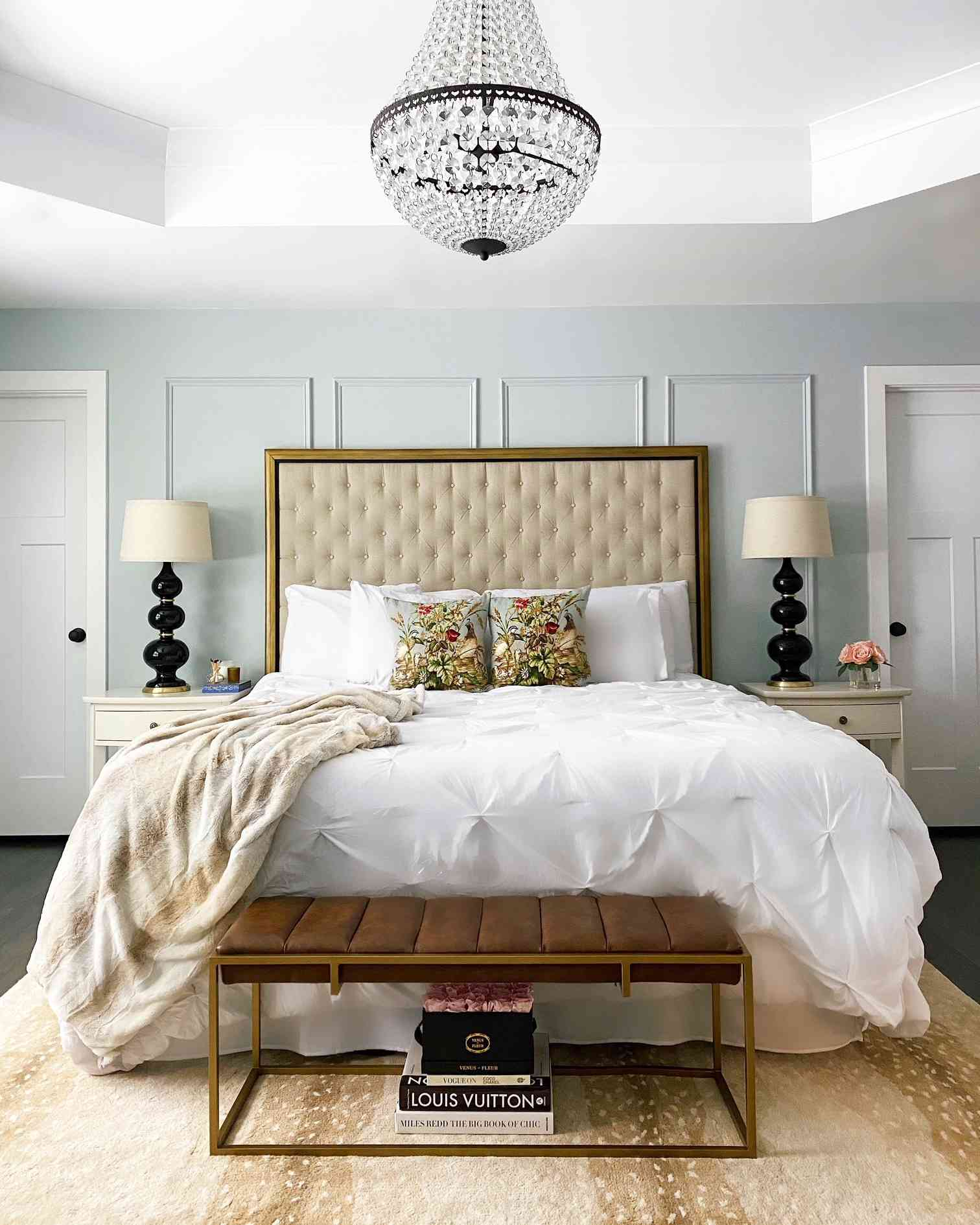 bedroom with pale blue walls brown and tan accents, glass chandelier