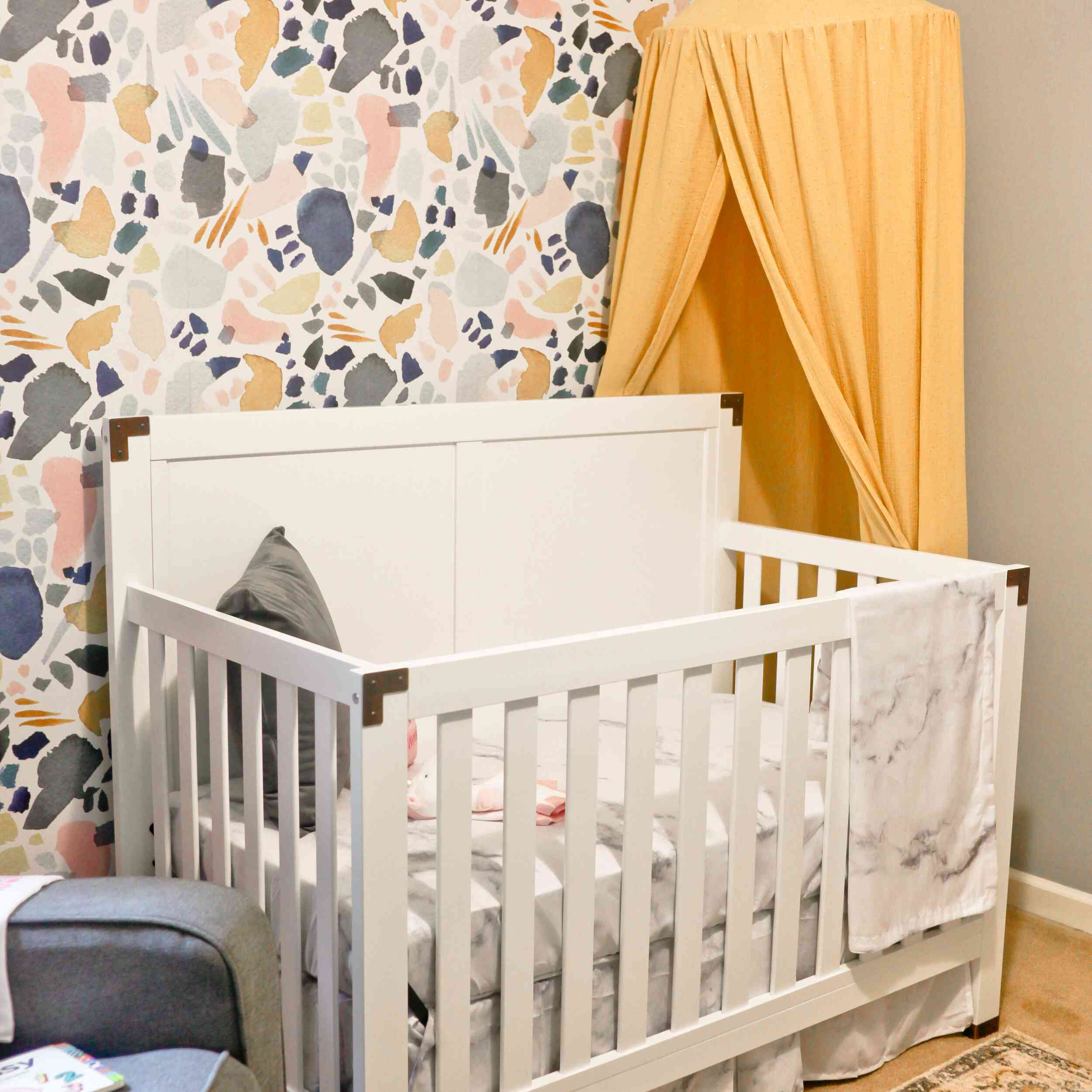 Nursery with mural wall and yellow accents
