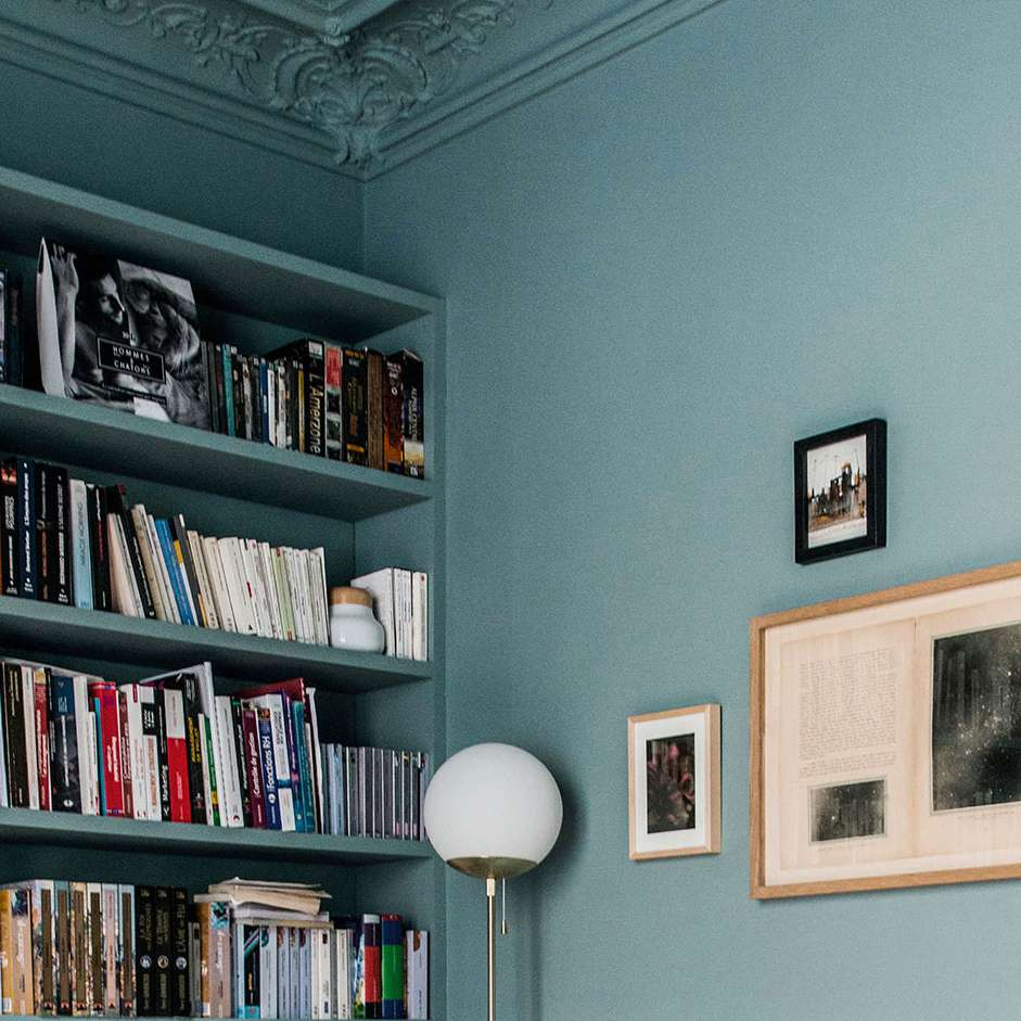 Bookshelf packed with books and art on wall.
