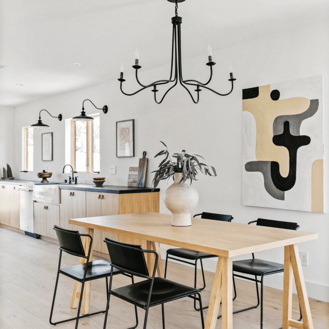 An open-concept dining room with a black chandelier that coordinates with the lights in the kitchen