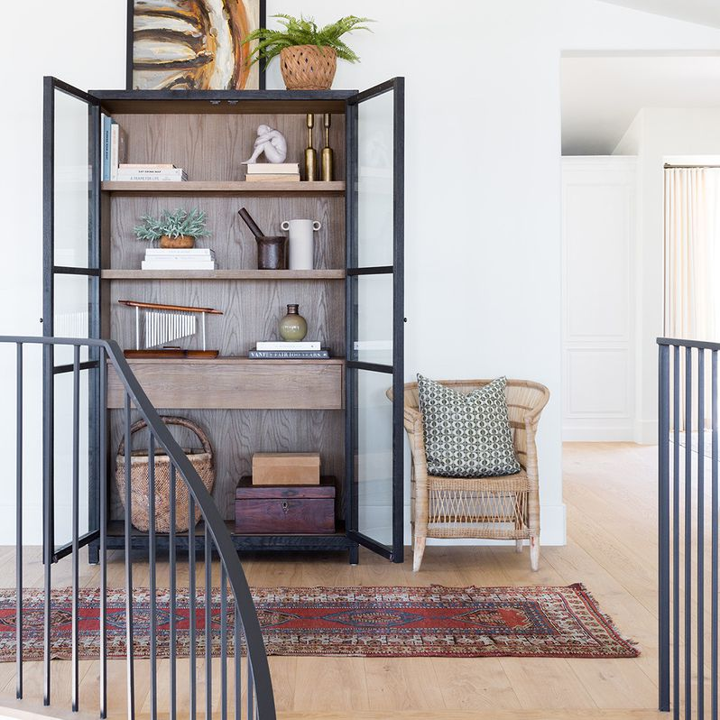 Modern boho chic hallway with a styled cabinet, vintage chair, and Turkish rug