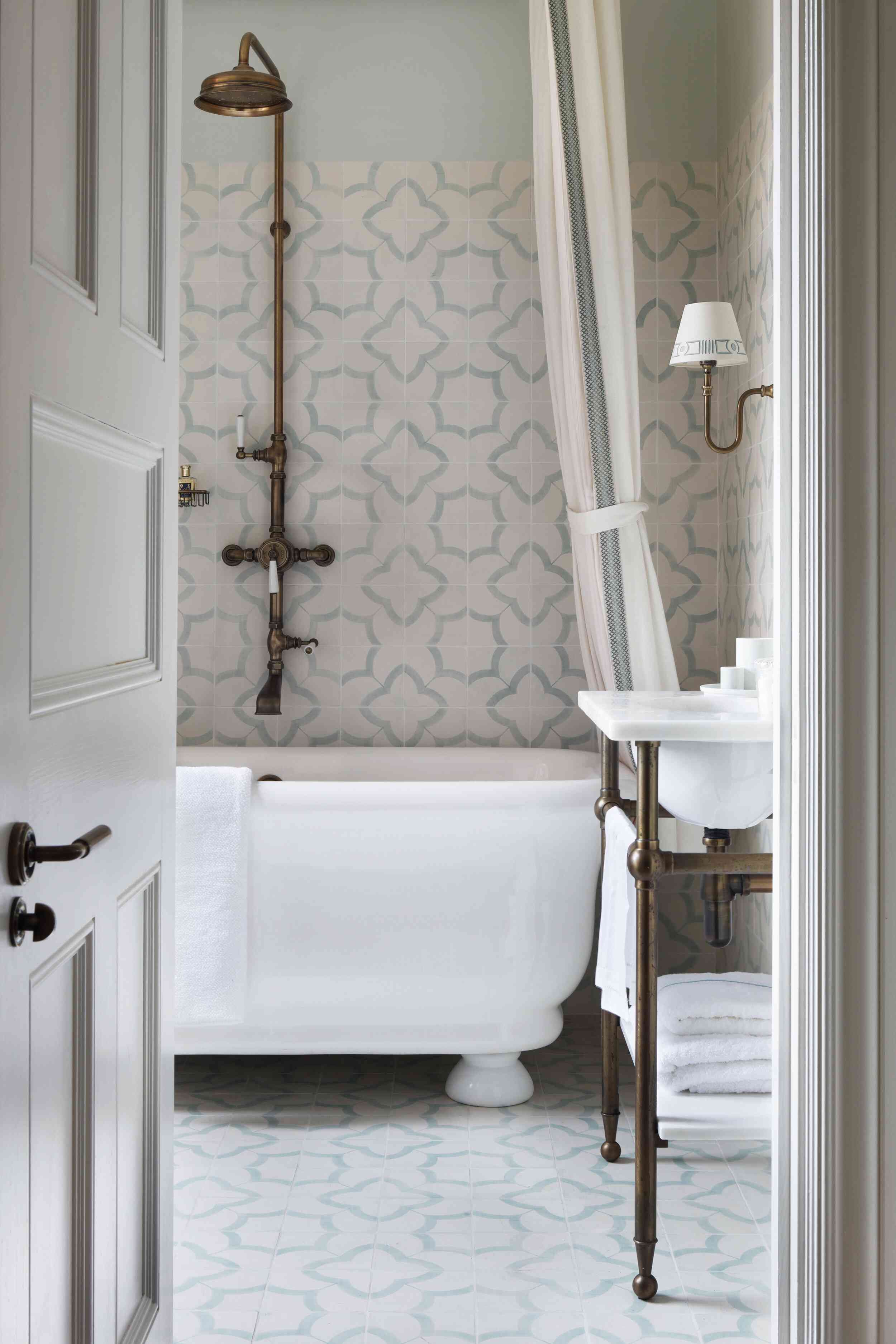 A small primary bathroom lined with pretty printed tiles