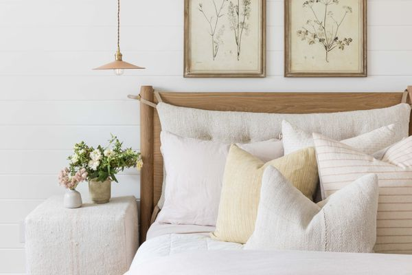 Soft neutral bed with yellow pillows.