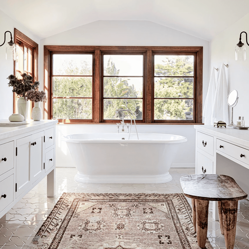 A large bathroom with two vanities, a freestanding tub, and a pink printed rug