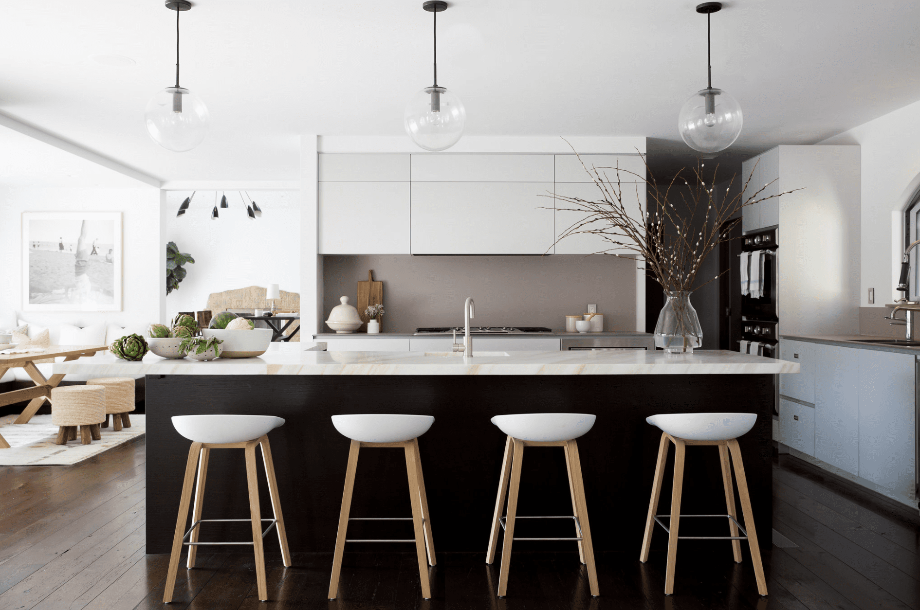 A black and white kitchen with a bold taupe backsplash
